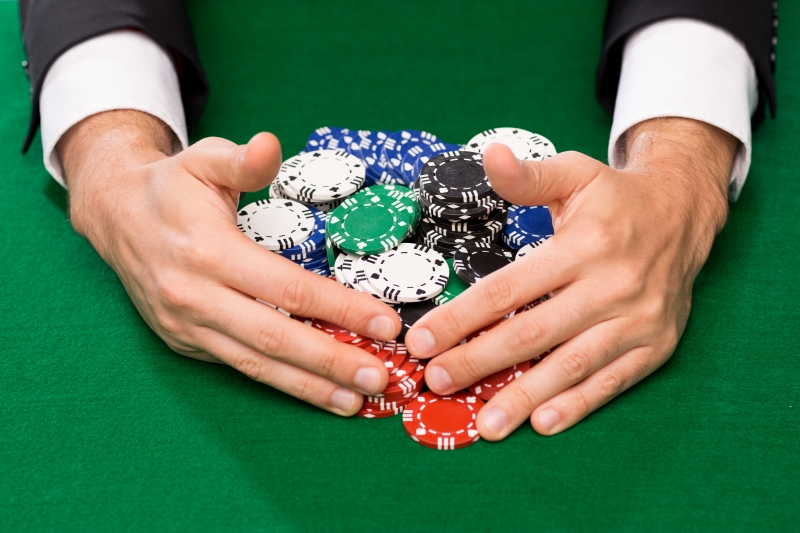 10580352-poker-player-with-chips-at-casino-table